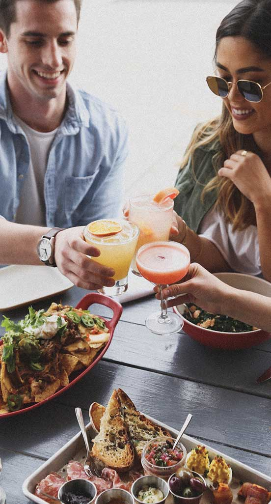 Diners toasting drinks over plates of food